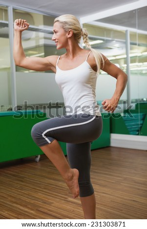 Side view of a smiling young woman doing power fitness exercise at yoga class - stock photo