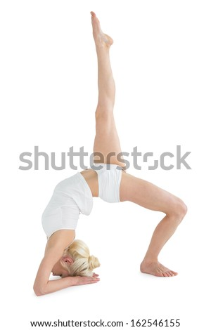 Side view of a sporty young woman stretching body with raised leg against white background - stock photo