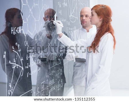 side-view of a student in a chemistry lab writing on a blackboard formulas  under her teacher supervision - stock photo