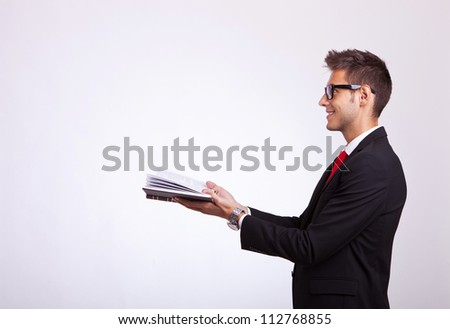 side view of a student looking at something imaginary comming out of his book - stock photo