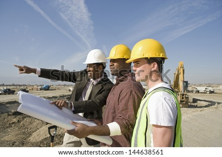 Side view of a surveyor and construction workers in hard hats with plans on site - stock photo
