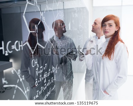 side-view of a teacher in a chemistry lab analyzing formulas written by a student  looking happy in the camera on a blackboard - stock photo