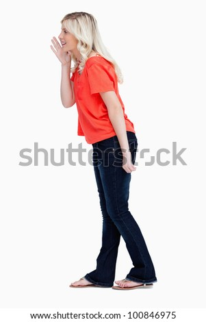Side view of a teenager girl calling for someone against a white background - stock photo