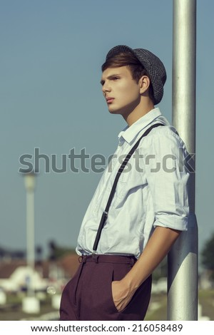 Side view of a thoughtful young guy posing with hand in pocket and rolled up sleeves, wearing hat, shirt and trousers with suspenders, looking away while leaning his back against a street lamp pillar. - stock photo
