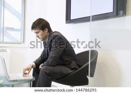 Side view of a tired businessman using laptop in waiting room - stock photo