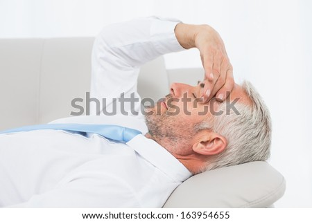 Side view of a tired mature businessman resting on sofa in the living room at home