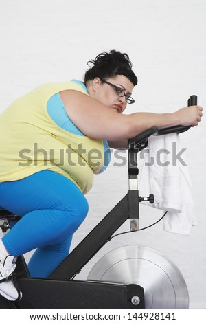 Side view of a tired overweight woman on exercise bike against white background - stock photo
