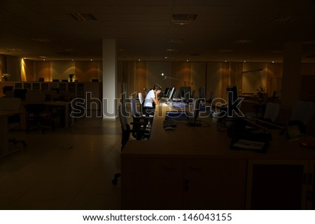 Side view of a tired young woman working at computer in dark office - stock photo