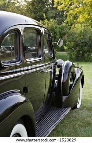 Side view of a vintage black Buick Sedan.  1930's?  Running board, fender, white all tires. - stock photo