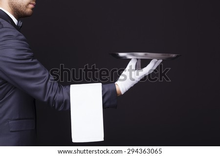 Side view of a waiter holding an empty silver tray against dark background