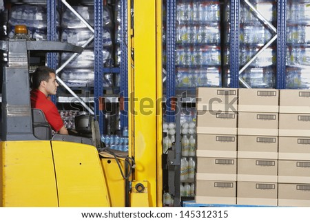 Side view of a warehouse worker operating forklift