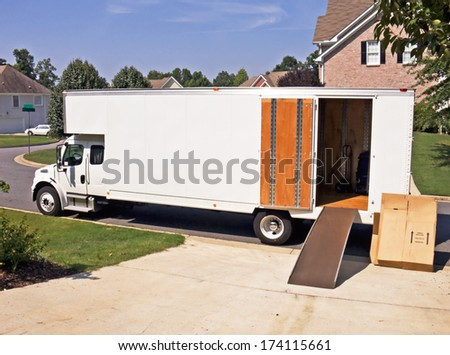 side view of a white moving and storage truck with an open door and cardboard boxes stacked against the side.  - stock photo