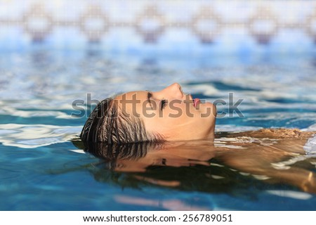 Side view of a woman face relaxing floating on water of a swimming pool or spa - stock photo