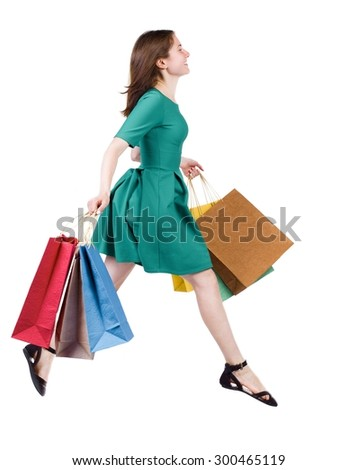 side view of a woman jumping with shopping bags. beautiful brunette girl in motion.   Isolated over white background. The girl in stylish green dress ambled happily flying with shopping bags. - stock photo