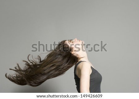 Side view of a woman with long brown hair blowing in wind against gray background - stock photo