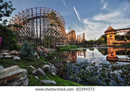 Side view of a wooden roller coaster being mirrored in a lake with blue, clear sky - stock photo
