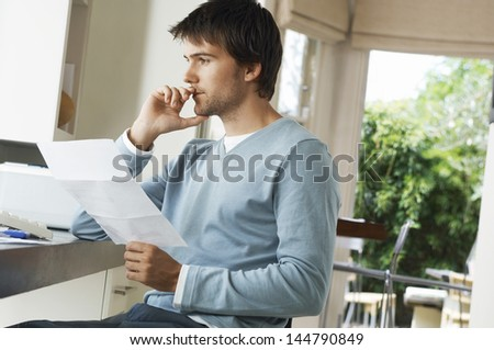 Side view of a worried young man holding bill at home - stock photo