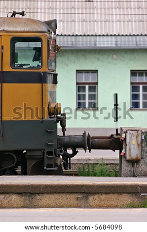Side view of a yellow railway engine parked at a station, with a green building in the background. Taken at Ljubljana station in Slovenia. - stock photo