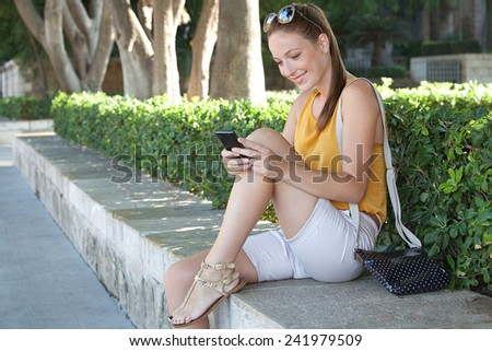 Side view of a young and beautiful tourist woman sitting in a green park holding and using her smartphone to network while visiting a destination city on holiday. Travel and lifestyle technology. - stock photo