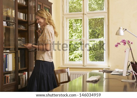 Side view of a young blond woman looking in cabinet in study room