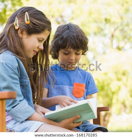 Side view of a young boy and girl reading book on park bench