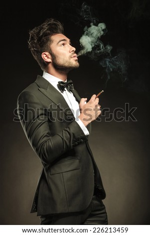 Side view of a young business man blowing smoke while holding a cigarette in his right hand. Looking up, on black studio background. - stock photo