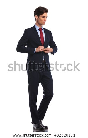 side view of a young business man closing his coat and looks away from the camera on white background
