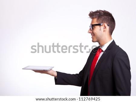 side view of a young business man holding a touch screen pad and looking up above it - stock photo