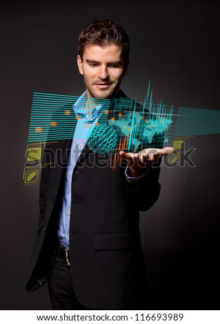 side view of a young business man holding a touch screen pad and looking up above it at some symbols and words coming out of it - stock photo