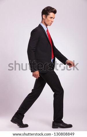 side view of a young business man walking and looking forward, on a gray background - stock photo