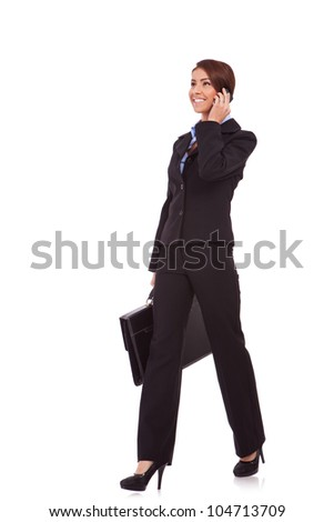 side view of a young business woman talking on the phone and holding a brief case while walking on white background - stock photo
