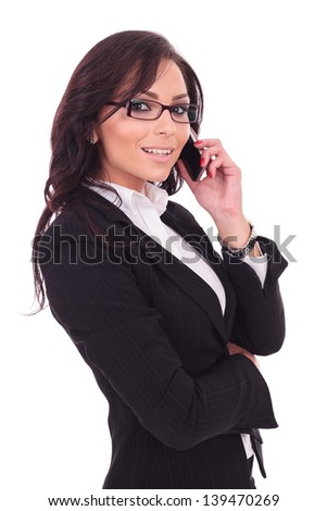 side view of a young business woman talking on the phone while smiling to the camera. on white background