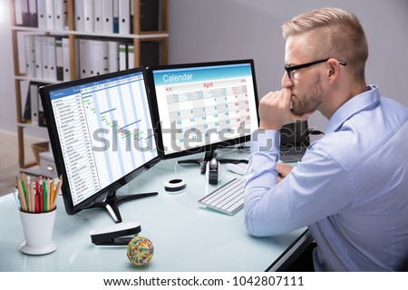Side View Of A Young Businessman Looking At Gantt Chart On Computer In Office