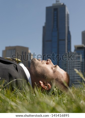 Side view of a young businessman lying on grass against office buildings - stock photo