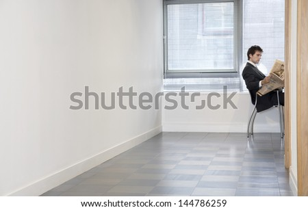 Side view of a young businessman reading newspaper in an empty room