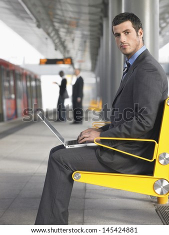 Side view of a young businessman using laptop at the train station - stock photo