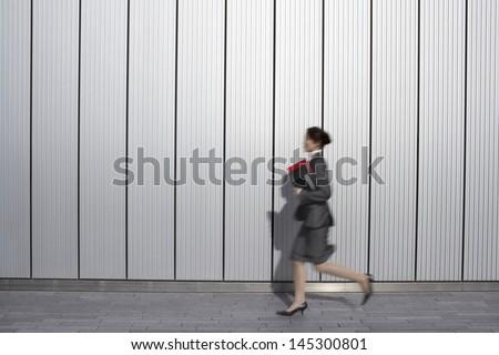 Side view of a young businesswoman running past building with folders - stock photo