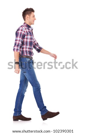 side view of a young casual man walking forward, on white background - stock photo