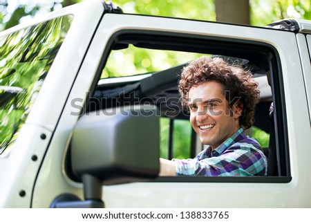 Side view of a young cheerful Caucasian man enjoying a car ride. - stock photo