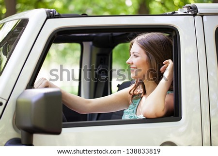 Side view of a young cheerful Caucasian woman enjoying a car ride. - stock photo
