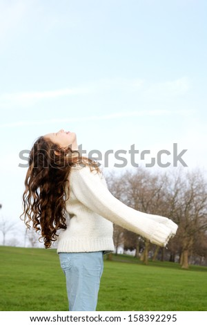 Side view of a young child girl leaning back and looking up at a blue sky while in a green grass park with leafless trees, playing during a sunny winter day, outdoors. - stock photo