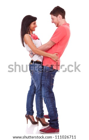 Side view of a young couple holding each other by the waist , face to face, and smiling - stock photo