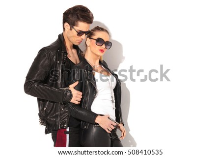 side view of a young couple in leather jackets and sunglasses , standing embraced on white background