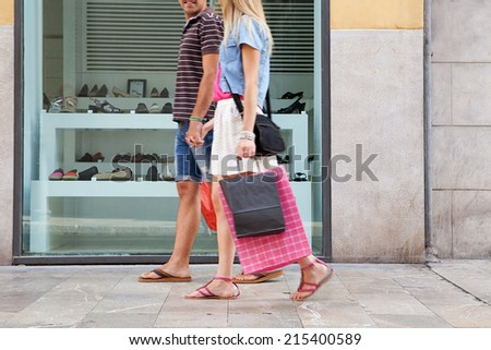 Side view of a young couple lower body section walking in shopping street with a shoe store window display, carrying shopping bags and spending money on holiday. Consumer lifestyle, outdoors. - stock photo