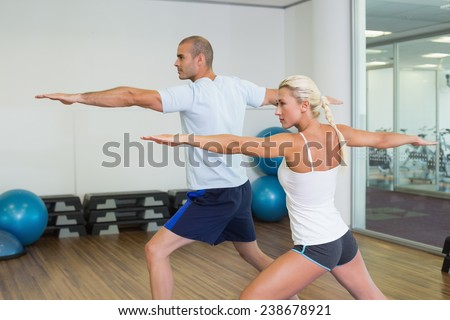 Side view of a young couple stretching hands in yoga class - stock photo