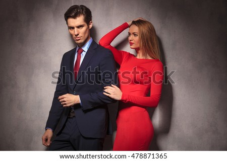 side view of a young elegant couple , woman in red dress looking at her lover in suit and tie