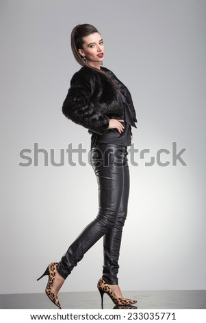 Side view of a young elegant fashion woman posing on grey studio background with her hands around her waist and one leg in the back. - stock photo