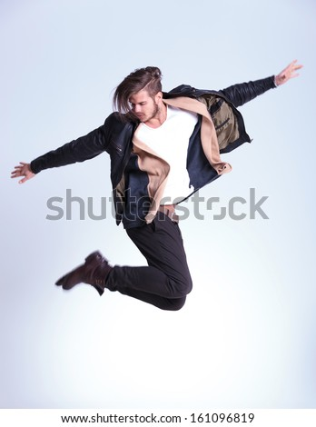 side view of a young fashion man in leather jacket jumping in studio - stock photo