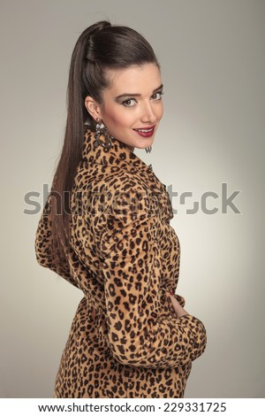 Side view of a young fashion woman wearing a animal print coat, smiling for the camera.
