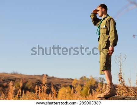 Side View of a Young Handsome Boy Scout Standing on the Rock and Watching Over the Wide Field - stock photo